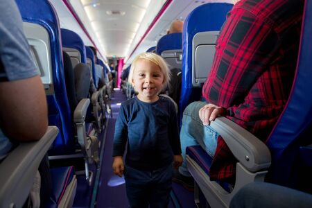 Cute toddler boy in airtplane, playing on the path between the seats, smiling happily. Family travel with kids concept Reklamní fotografie