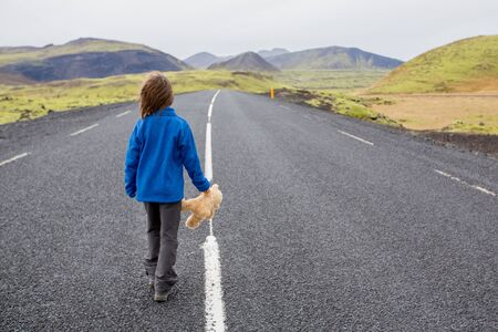 Cute preshool boy with teddy bear in hand, running on a road in Iceland on a rainy day Stok Fotoğraf