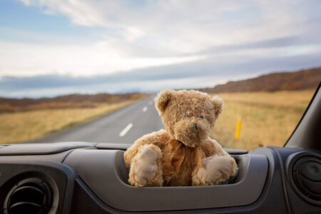 Teddy bear, sitting on the front windshield of a camper van, people traveling in Iceland, camping, autumntime Foto de archivo