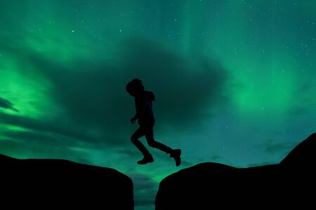 Sillhouette of preschool child, jumping over gap on aurora borealis sky background, Iceland