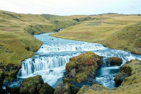 Beautiful view of the Skogafoss waterfall in Iceland on a sunset cloudy day, autumntime