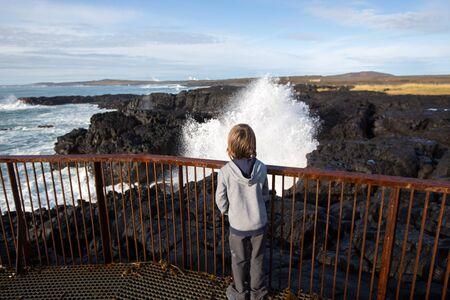Children watching gig waves crashing in rocks on the south west coast on Iceland, near Gunnuhver