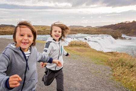 Portrait of happy running kids, boy brothers, near smaller waterfall around Gullfoss, Iceland autumntime
