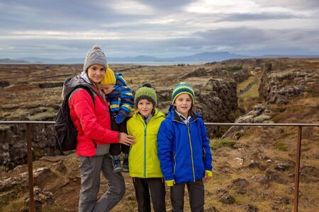 Mother with children, walking on a path in scenic Thingvellir National Park rift valley, Iceland autumntime