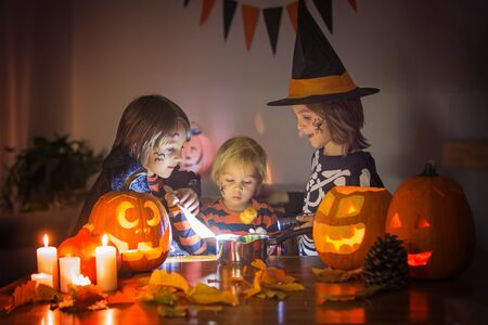 Children, boy brothers, playing with carved pumpkin at home on Halloween, making magic potion