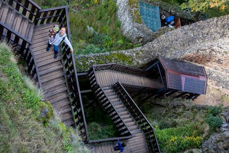 Wodeen staircase, going to castle in the forest, people walking downstairs