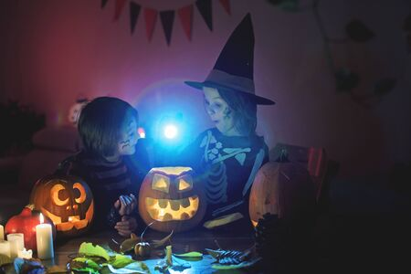 Kinder, junge Brüder, die an Halloween zu Hause mit geschnitztem Kürbis spielen und Zaubertrank herstellen Standard-Bild