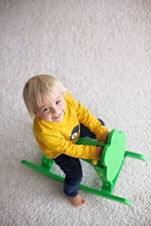 Little cute toddler boy, playing with rocking frog swing at home in kids room Standard-Bild