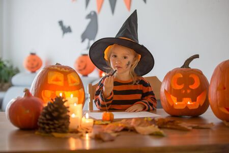 Adorable child, toddler girl, drawing Halloween carved pumpkin and playing with decoration at home 스톡 콘텐츠 - 132362654