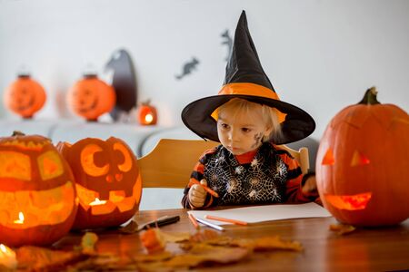 Child, toddler boy, drawing with pasteles pumpkin at home on Halloween, halloween carved pumpkin on the table, decoration on the wall 스톡 콘텐츠