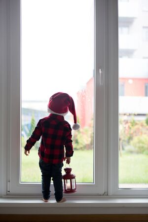 Toddler child, boy, standing in front of a big french doors, leaning against it looking outside, holding lantern