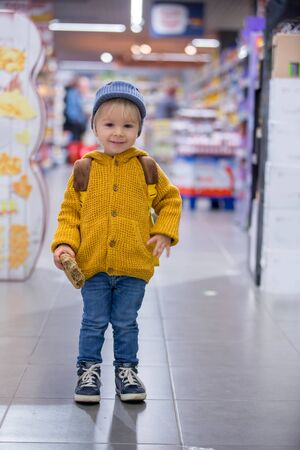 Fashion toddler boy with backpack, shopping in supermarket shop Imagens