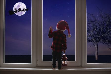 Toddler child standing in front of a big french doors, leaning against it looking at night sky and Santa Claus, holding lantern