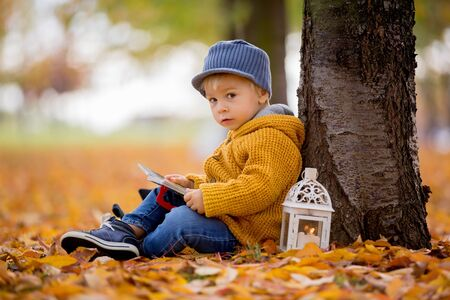 Beautiful fashion toddler boy, reading a book in park with lantern in hand and backpackon his back Stock Photo