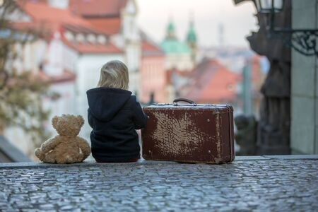 Beautiful child with old vintage suitcase and teddy bear, casually dressed, looking at night view of Prague city, wintertime