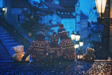 Beautiful children, three boy brothers, casually dressed, looking at night view of Prague city, wintertime