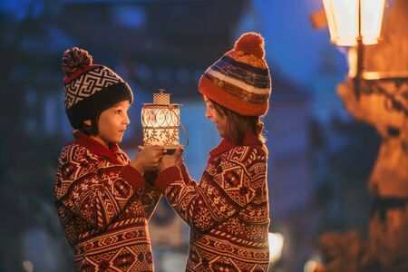 Beautiful children, boy brothers holding lantern, casually dressed, looking at night view of Prague city, wintertime Stock Photo