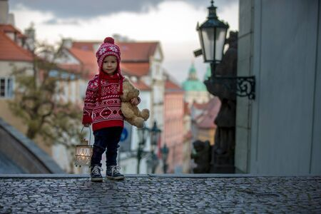 Beautiful toddler child with lantern and teddy bear, casually dressed, looking at night view of Prague city, wintertime Stock Photo