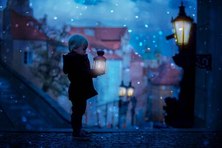 Beautiful toddler child with lantern and teddy bear, casually dressed, looking at night view of Prague city, wintertime Imagens
