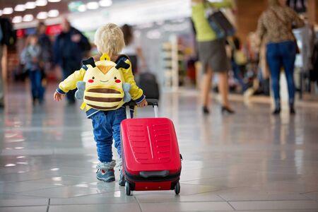 Lindo bebé esperando el embarque para volar en la sala de tránsito del aeropuerto cerca de la puerta de salida. Viaje de estilo de vida familiar activo en avión con el niño de vacaciones