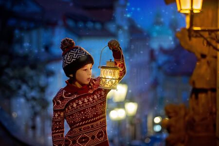 Beautiful preschool child, holding lantern, casually dressed, looking at night view of Prague city, wintertime Stock Photo