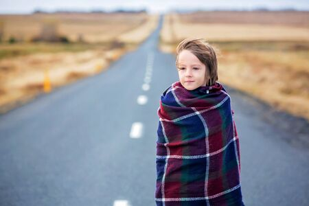 Beautiful child, standing on a road on a very windy day, wrapped in scarf, watching the sunrise in Iceland, autumntime Stok Fotoğraf