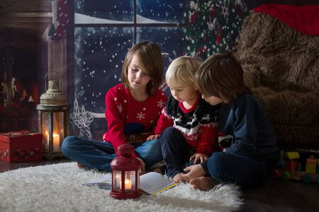 Three children, boy brothers, reading a book at Chrismas night in a cozy room on candles
