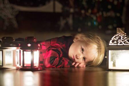 Lieve peuter die thuis met kaarsen op de grond ligt te wachten op kerstnacht