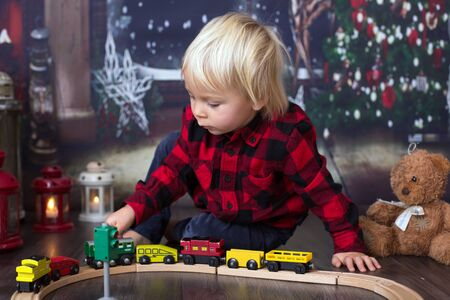 Sweet toddler boy,playing with wooden train at home at night on Christmas night Stock Photo