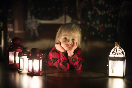 Sweet toddler boylying on the floor at home with candles, waiting for Christmas night