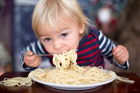 Sweet toddler child, boy, eating spaghetti at home on Christmas