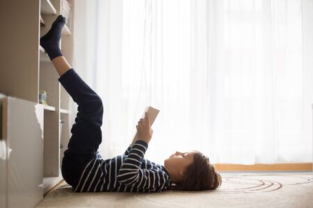 Cute child, boy, reading a book at home, happy to learn
