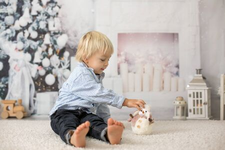Blond toddler child, boy, reading a book at home, lying on the floor with a toy 스톡 콘텐츠
