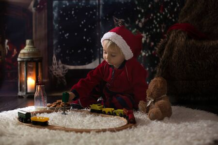 Sweet toddler boy,playing with wooden train at home at night on Christmas night Standard-Bild