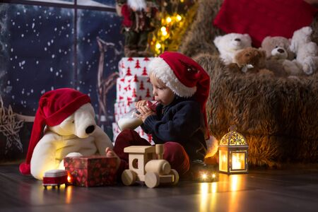 Boy playing with wooden train at home at night on Christmas night