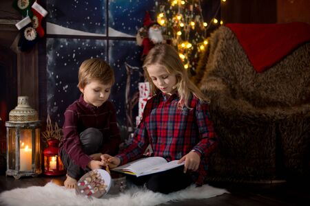 Cute preschool girl and boy, siblings, sitting next to christmas tree, opening presents and reading book at Christmas night