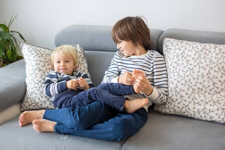 Little toddler and his older brother, having fun at home, tickling and giggle happily