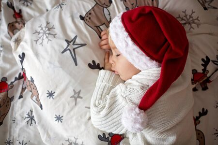 Sweet beautiful blond toddler boy, sleeping in bed with toy on Christmas