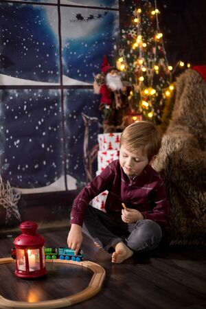 Cute preschool boy, sitting next to christmas tree, playing with toys on Christmas night Stock Photo