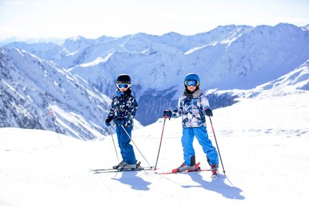 Happy people, children and adults, skiing on a sunny day in Tyrol mountains. Kids having fun while skiing Foto de archivo