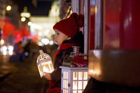 Sweet little toddler boy, holding lantern and a teddy bear at night in Prague at Christmas