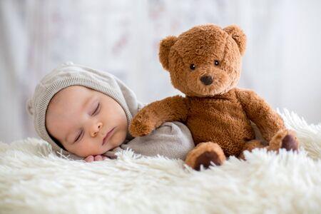 Süßes Baby im Bären insgesamt, schlafend im Bett mit Teddybär-Stofftieren, Winterlandschaft hinter ihm