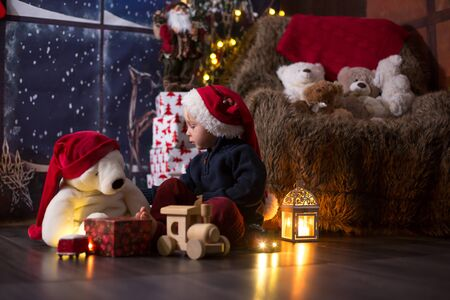 Sweet toddler boy, playing with wooden train at home at night on Christmas night