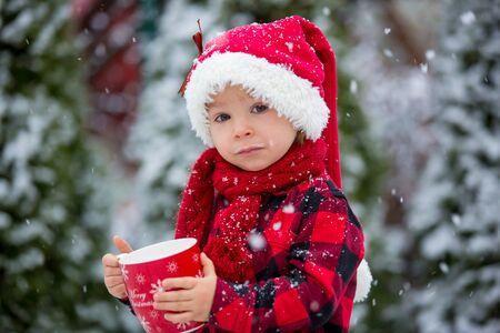 Süßer schöner Kleinkindjunge, der eine Tasse mit heißer Milch hält, draußen im Schnee trinkt, Winter- und Weihnachtsferien genießt