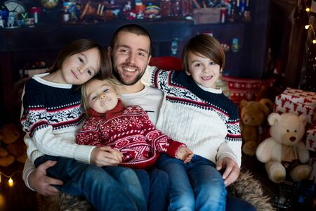 Christmas family portirat at home, father with three kids in chair 写真素材