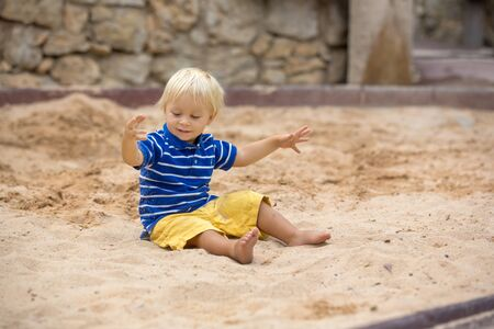 Little toddler boy, playing with sand in sandpit at the playground summertime