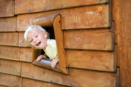 Curious child, toddler boy, peering from a small window in wooden shrub, making funny face Stock fotó