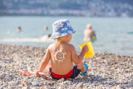 Sweet toddler child, boy, holding beach toys, with sunscream applied on his back, ready for the harsh sun on the beach