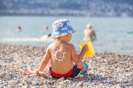 Dulce niño pequeño, niño, sosteniendo juguetes de playa, con protector solar aplicado en su espalda, listo para el duro sol en la playa