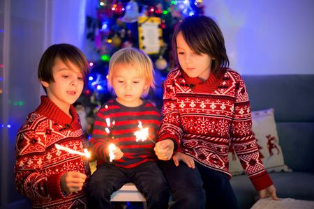 Waist up portrait of happy children celebrating New Year together and lighting sparklers at home